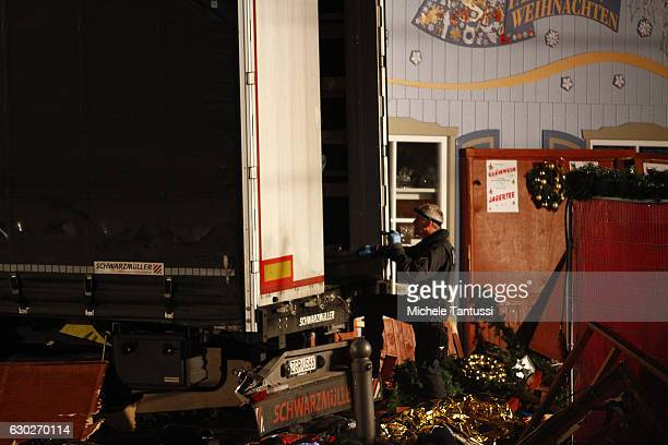 Security and rescue workers inspect a lorry truck after it was ploughed through a Christmas market on December 19 2016 in Berlin Germany Several...