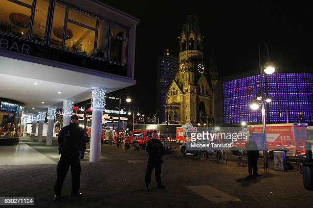 Security and rescue workers tend to the area after a lorry truck was ploughed through a Christmas market on December 19 2016 in Berlin Germany...