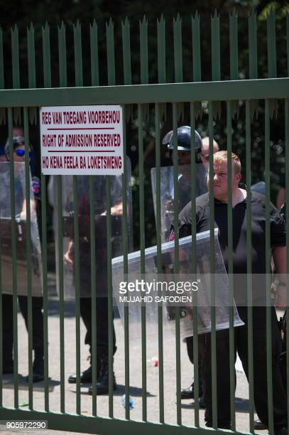 Security and South African police protect the main entrance of the Overvaal Afrikaans learning school as protesters including disgruntled parents...