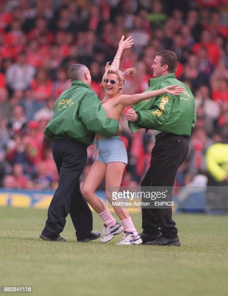 Security at the Leeds United ground remove a female streaker from the pitch