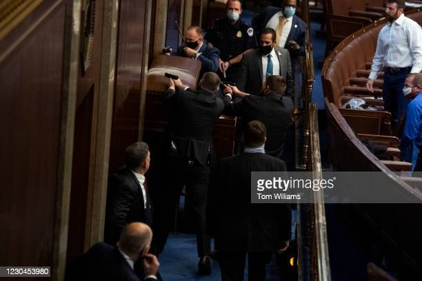 Security barricades the door of the House chamber as protesters disrupt the joint session of Congress to certify the Electoral College vote on...