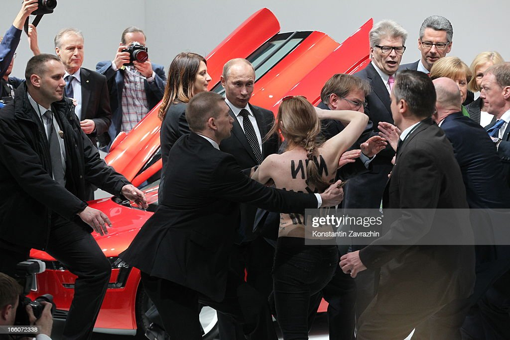 Security block an attack by an activist of the Ukrainian women rights group 'Femen' as Russian President Vladimir Putin and German Chancellor Angela Merkel attend the opening of the industrial exhibition 'Hannover Messe' on April 8, 2013 in Hannover, Germany. Russia is the official partner Country of this year's fair with more than 160 Russian companies showcasing their latest industrial products and solutions.