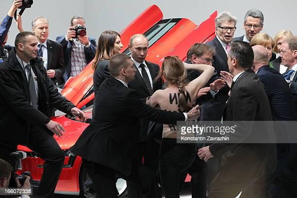 Security block an attack by an activist of the Ukrainian women rights group 'Femen' as Russian President Vladimir Putin and German Chancellor Angela...
