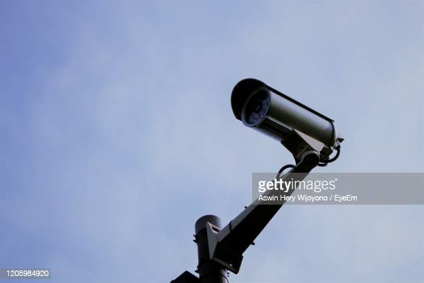 security camera against blue sky - big brother orwellian concept stock pictures, royalty-free photos & images