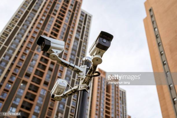 security camera against residential buildings background - business security camera stock pictures, royalty-free photos & images