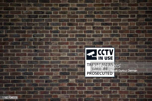 """""""Security camera in use"""" sign. """"Trespassers will be prosecuted"""" sign on a brick wall in London"""
