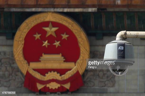 A security camera is seen in front of the Chinese national emblem outside the Great Hall of the People where sessions of the Chinese People's...
