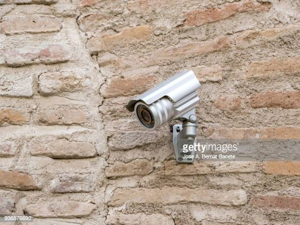 Security camera on an ancient wall of bricks.