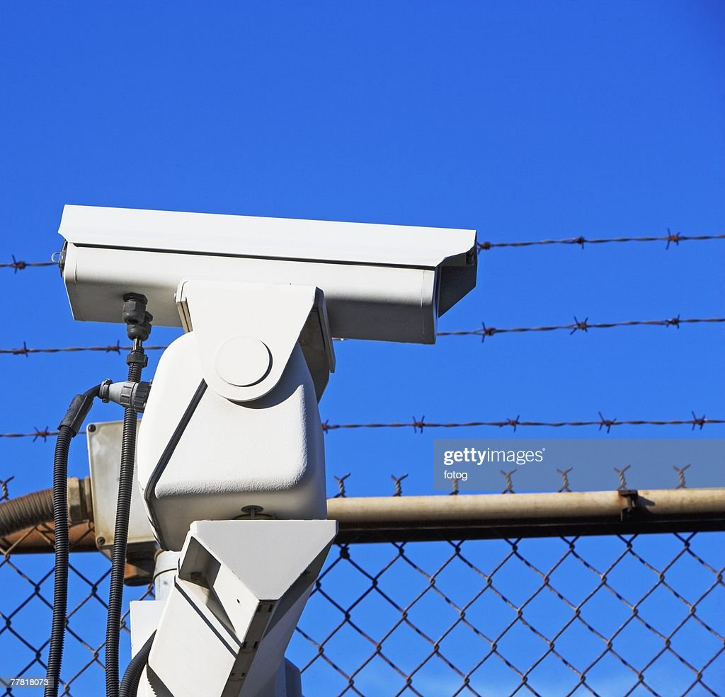 Security camera on fence stock photo getty images