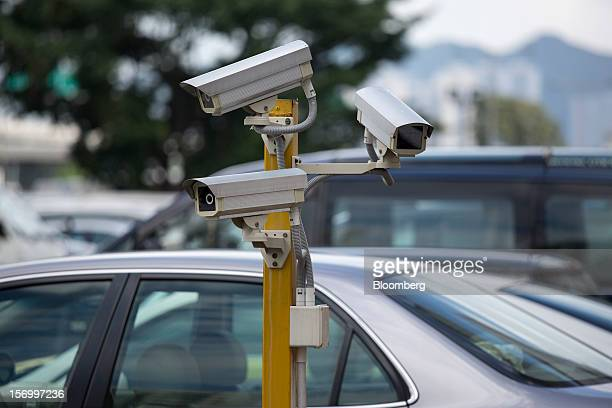 Security cameras operate in a parking lot in Hong Kong China on Thursday Nov 22 2012 Investors reacting to the Hong Kong government's campaign to...