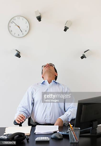 Security cameras watching office worker