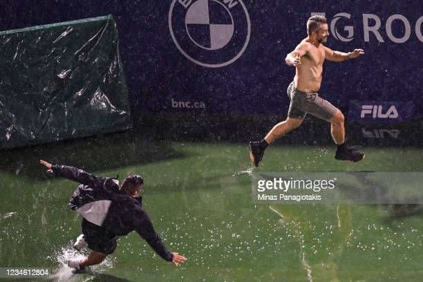 Security chase a spectator on centre court during a rain delay on Day Two of the National Bank Open presented by Rogers at IGA Stadium on August 10,...