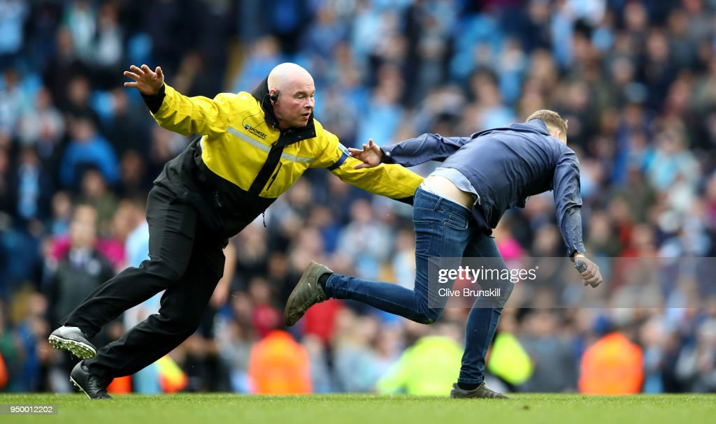 Security chase fans as they invade the pitch following the Premier League match between Manchester City and Swansea City at Etihad Stadium on April 22, 2018 in Manchester, England.