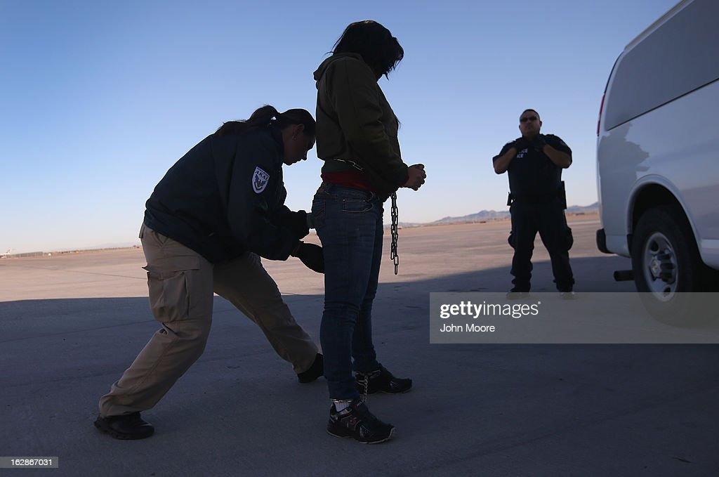 A security contractor frisks a female immigration detainee from Honduras ahead of a deportation flight to San Pedro Sula, Honduras on February 28, 2013 in Mesa, Arizona. U.S. Immigration and Customs Enforcement (ICE), operates 4-5 flights per week from Mesa to Central America, deporting hundreds of undocumented immigrants detained in western states of the U.S. With the possibility of federal budget sequestration, ICE released 303 immigration detainees in the last week from detention centers throughout Arizona. More than 2,000 immigration detainees remain in ICE custody in the state. Most detainees typically remain in custody for several weeks before they are deported to their home country, while others remain for longer periods while their immigration cases work through the courts.