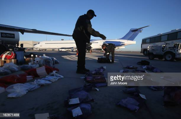 A security contractor hired by US Immigration and Customs Enforcement counts bags of personal possessions of Honduran immigration detainees before...