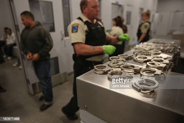 A security contractor hired by US Immigration and Customs Enforcement prepares to handcuff Honduran immigration detainees before their deportation...