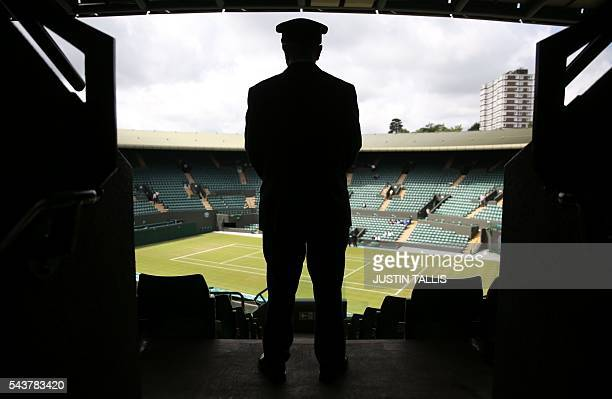 TOPSHOT A security contractor looks out over court 1 on the fourth day of the 2016 Wimbledon Championships at The All England Lawn Tennis Club in...