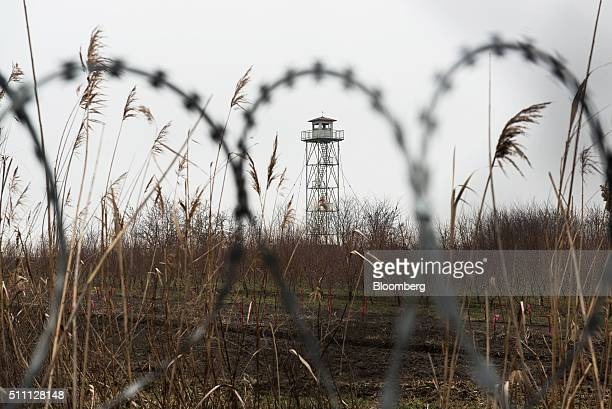 A security control post stands in the field beyond a razor wired topped security fence at the HungarianSerbian border near Roszke Hungary on...