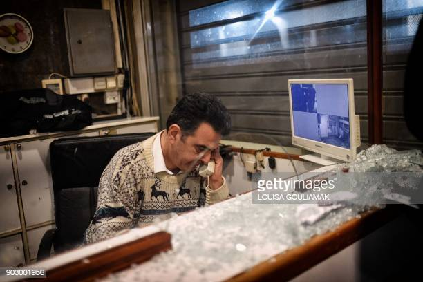 A security employee of the Labour Ministry makes a phone call by a shattered glass after Communistaffiliated PAME workers unionists stormed the...