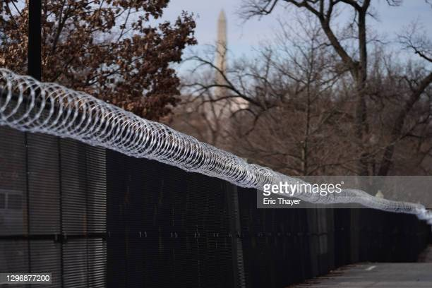 Security fencing runs down a street near the U.S. Capitol building, with the Washington Monument at top, on January 17, 2021 in Washington, DC. After...