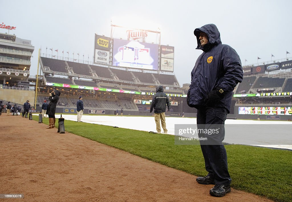 Security for the Minnesota Twins stands on the warning track as the tarp is on the field before the game between the Minnesota Twins and the Los Angeles Angels of Anaheim on April 17, 2013 at Target Field in Minneapolis, Minnesota. The game was postponed to a later date due to cold and rain.