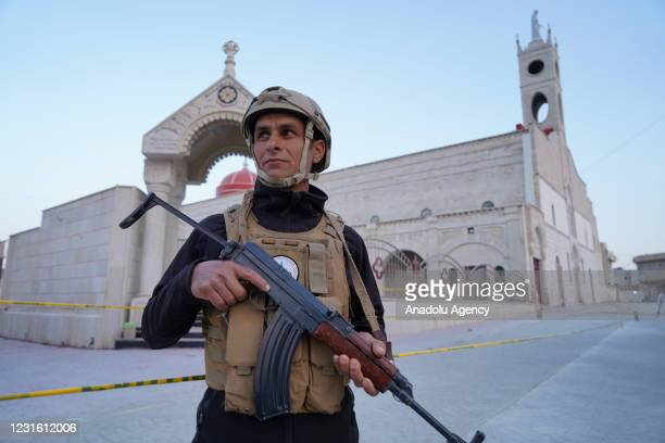 Security force guards the Syriac Catholic Church of the Immaculate Conception , in the predominantly Christian town of Qaraqosh , 32 kilometers...