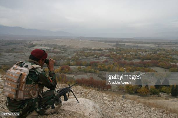 A security force member looks through binoculars as they protect a safe zone where approximately 9000 families fled from DaeshTaliban conflict in...