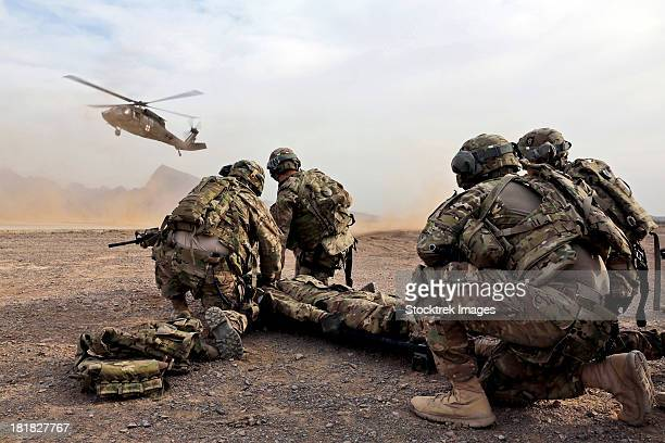 security force team members wait for a uh-60 blackhawk medevac helicopter. - batalha guerra - fotografias e filmes do acervo