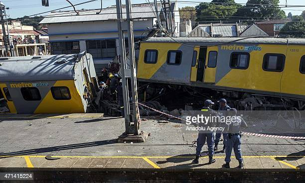 Security forces and rescuers work at the scene after two trains collided at Denver train station in Johannesburg South Africa on April 28 2015 The...