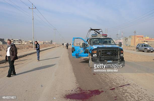 Security forces and residents stand at the scene of an explosion targeting a police forces vehicle in the multiethnic northern Iraqi city of Kirkuk...