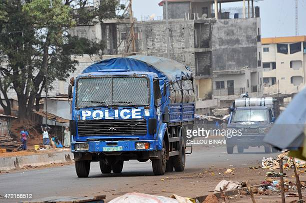 A security forces armoured truck and a police van patrol the streets during clashes with antigovernment protesters in Conakry on May 4 2015 More than...