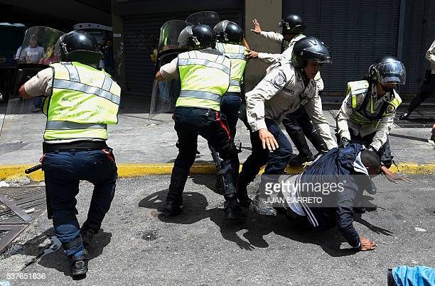 TOPSHOT Security forces arrest a man protesting against the severe food and medicine shortages in Venezuela in the surroundings of the Miraflores...