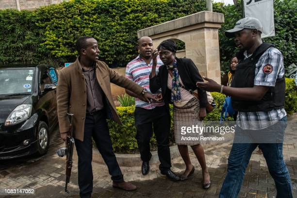 Security forces assist a women after she was rescued from the Dusit Hotel on January 15 2018 in Nairobi Kenya A current security operation is...