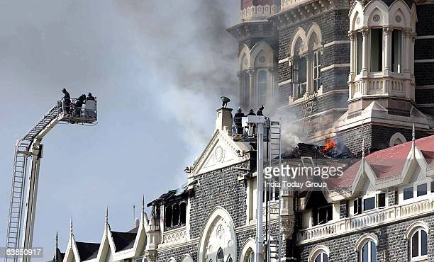 Security forces attend to a fire as it burns on the upper floors of the Taj Mahal Palace Tower Hotel during an armed siege on November 27 2008 in...