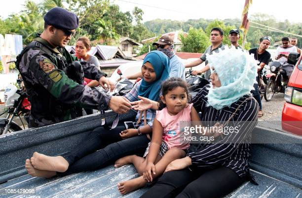 Security forces check identification at a checkpoint in Cotabato on the southern Philippine island of Mindanao on January 20 a day before a vote on...