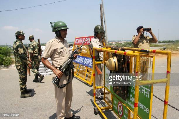 Security forces deployed at main junctions stand guard near a jail where controversial guru Ram Rahim Singh is awaiting sentencing in Rohtak on...