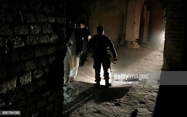Security forces inspect the explosion site after a bombing attack at a mosque in Herat Afghanistan on January 2 2017