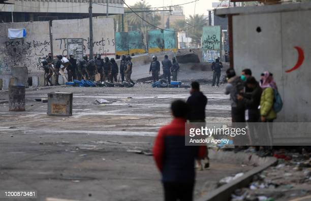 Security forces intervene in protesters with tear gas canisters during an anti-government protest at al-Khalani Square in Baghdad, Iraq on February...