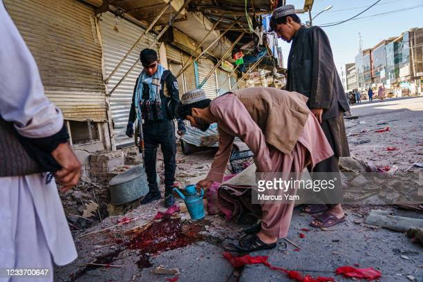 Security forces investigate the aftermath of a bomb explosion that killed 3 outside a bakery on Nawi Sarak Road, in Kandahar, Afghanistan, Friday,...