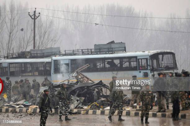 Security forces near the damaged vehicles at Lethpora on the JammuSrinagar highway on February 14 2019 in Srinagar India At least 30 CRPF jawans were...
