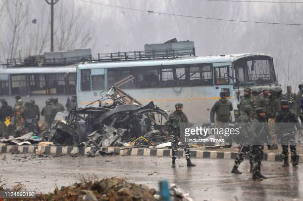 Security forces near the damaged vehicles at Lethpora on the Jammu-Srinagar highway, on February 14, 2019 in Srinagar, India. At least 30 CRPF jawans...