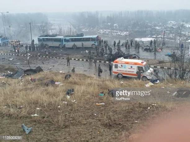 Security forces near the damaged vehicles at Lethpora on the JammuSrinagar highway on February 14 2019 in Srinagar India At Least 60 CRPF JAWANS were...