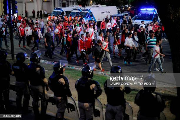 TOPSHOT Security forces stand guard as supporters of River Plate leave the Monumental stadium in Buenos Aires after authorities postponed the...