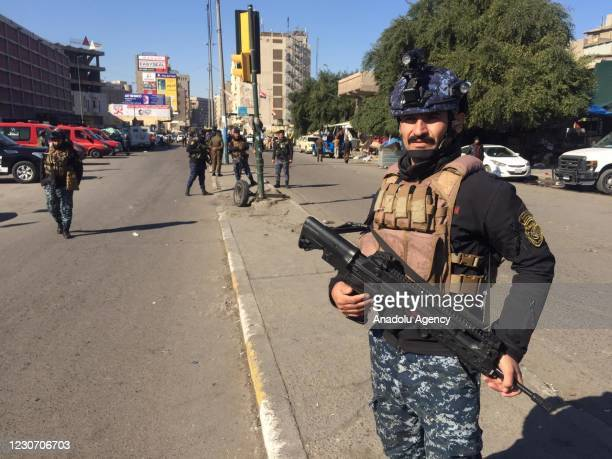 Security forces stand guard at the explosion site after a suicide bombing attack in Baghdad, Iraq on January 21, 2021.