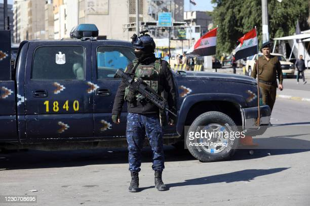 Security forces stand guard at the explosion site after a suicide bombing attack at al-Tayaran Square in Baghdad, Iraq on January 21, 2021. At least...