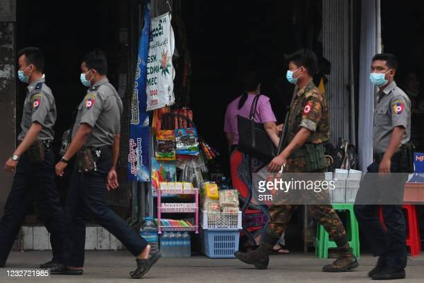Security forces walk past shops as they search for protesters, who were taking part in a demonstration against the military coup, in downtown Yangon...