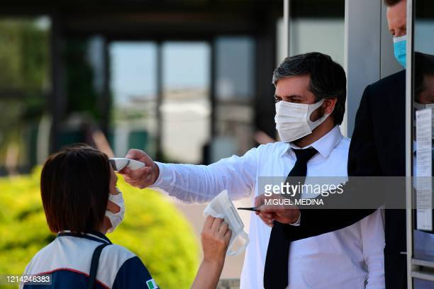 Security gard scans the body temperature of an employee, as another uses tweezers to hand her a face mask, as the employee arrives for her shift at...
