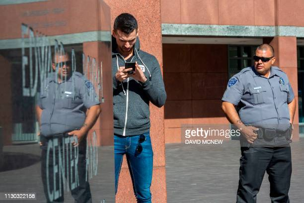 A security guard and a member of the media stand outside the Edward R Roybal Federal Building and US Courthouse where actress Lori Loughlin attended...