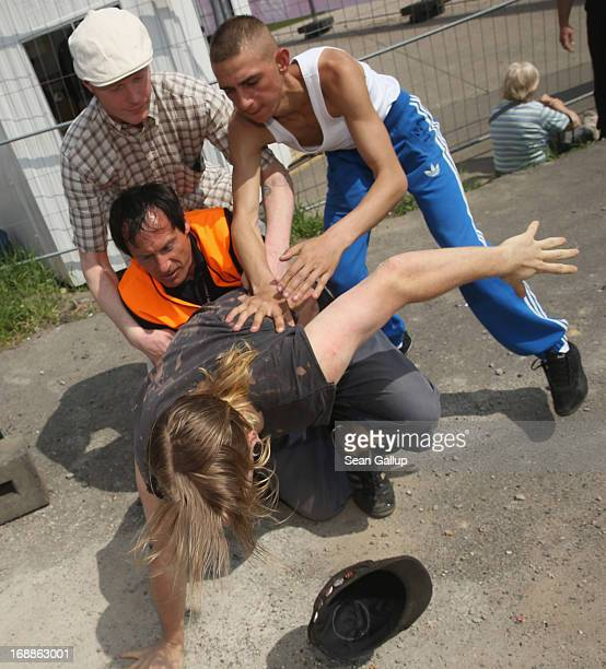 A security guard and an onlooker attempt to restrain a protester who had dunked a burning cross with a Barbie doll attached to it into a fountain...
