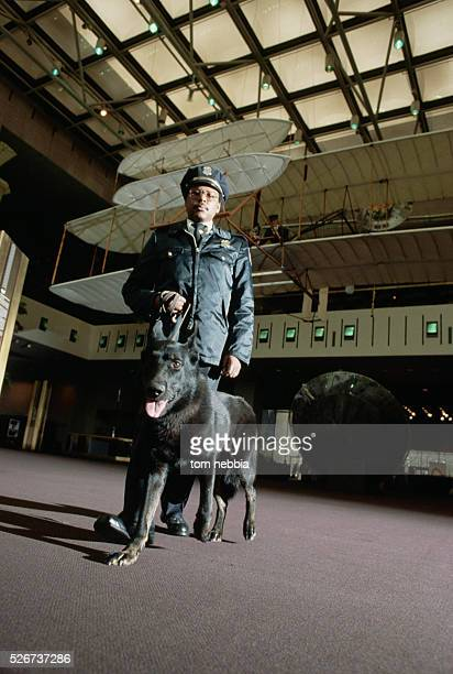 A security guard and dog stroll under the Wright Brothers display during their rounds at the National Air and Space Museum